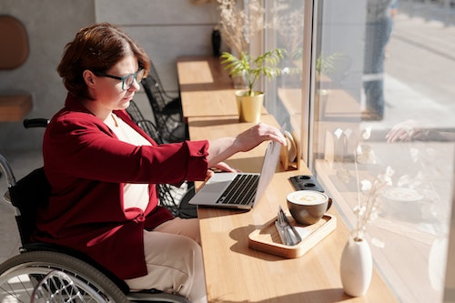 A professional in a wheelchair opens her computer at a sunny desk